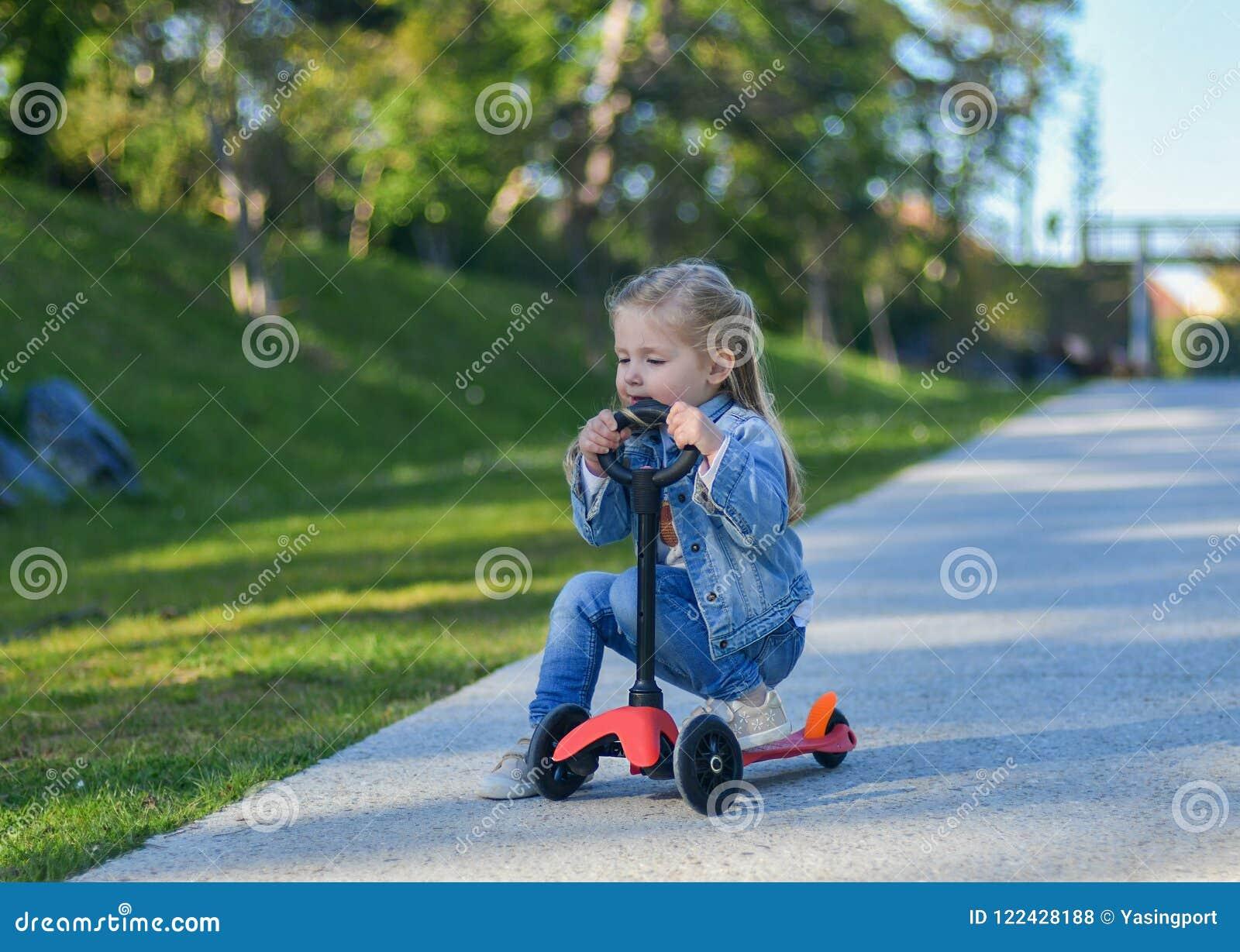 Het meisje berijdt een autoped