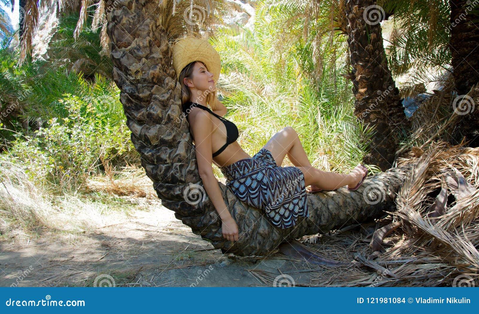 Het meisje in bikini en de hoed hebben rust in palmbos