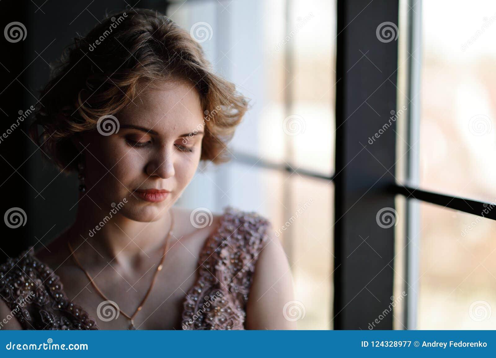 Het meisje het brunette in een mooie kleding stelt tegengesteld aan een venster