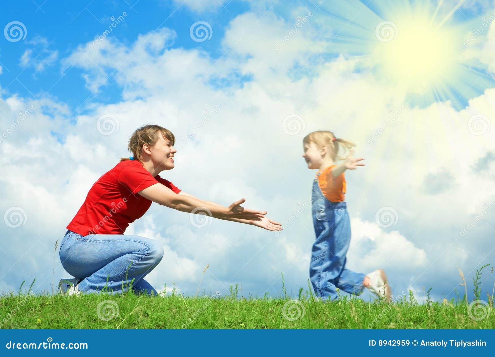 Het meisje dat aan moeder in werking wordt gesteld omhelst op groen gras