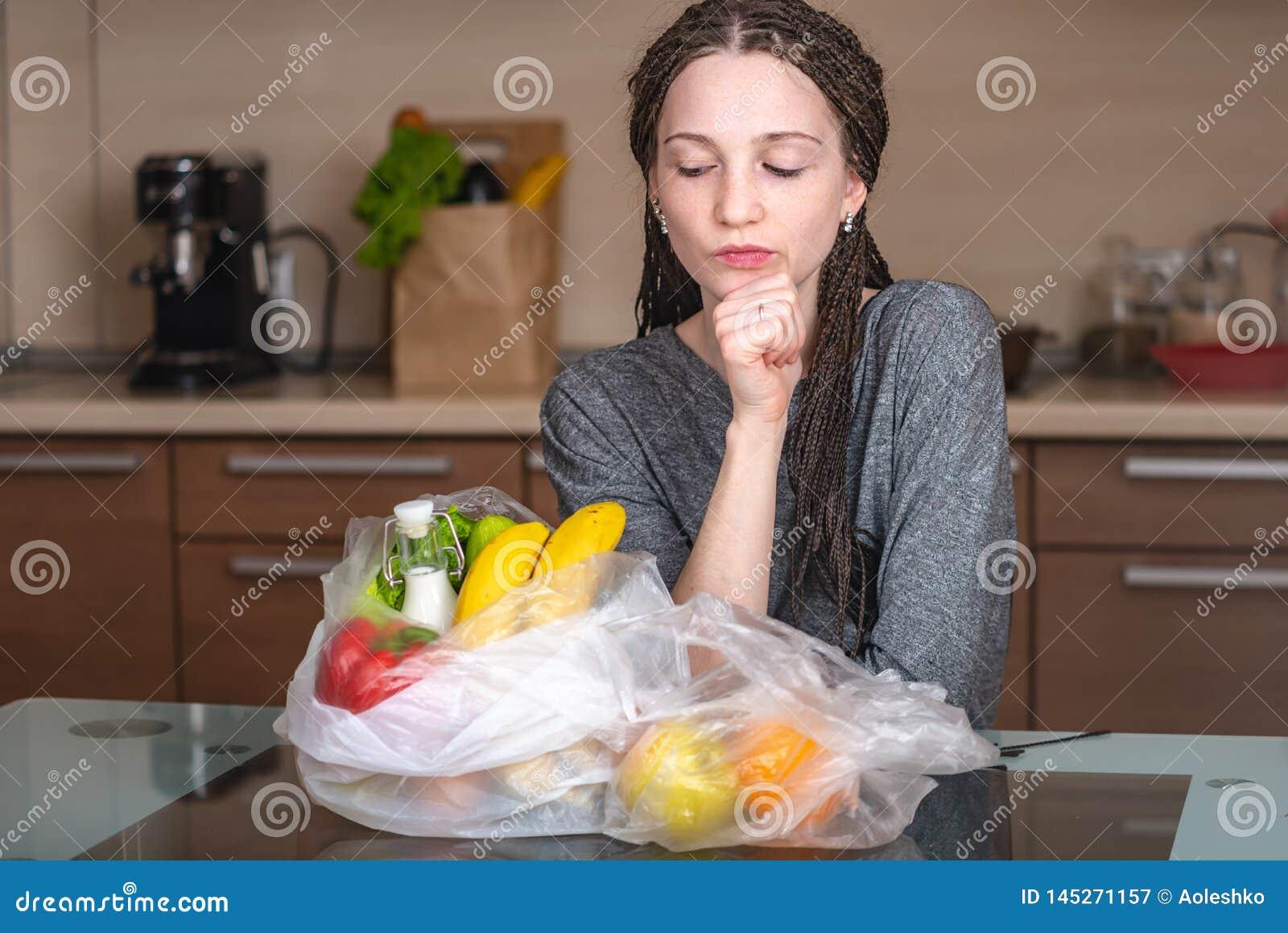 Het meisje denkt dat afval om een plastic zak te gebruiken om producten te kopen Milieubescherming en het verlaten van plastiek