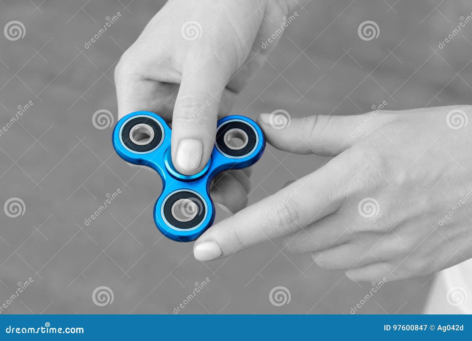 Het meisje die blauwe metaalspinner in handen op de straat spelen, vrouwelijke handen die populair friemelt spinnerstuk speelgoed