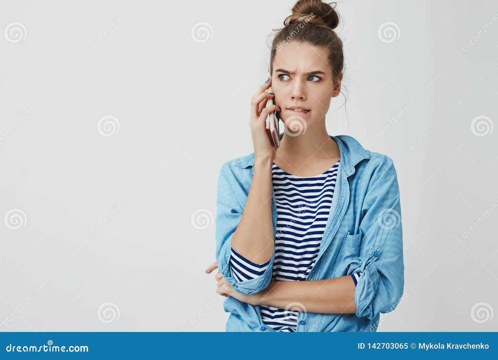 Het meisje die taaie lastige keus onder ogen zien verwarde het bijten het lagere lip fronsen kijkend opzij ernstig houdend smartp