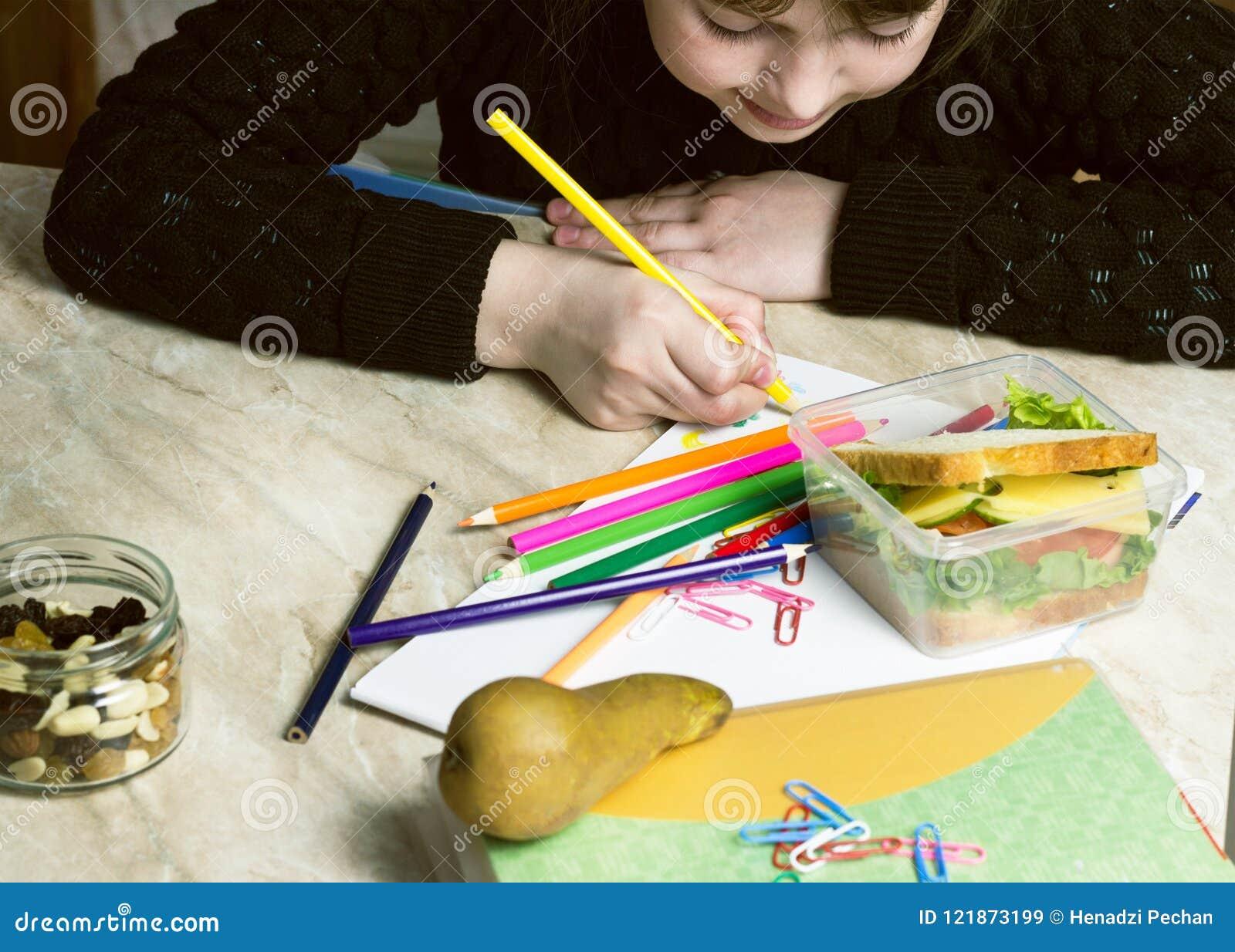Het meisje doet de lessen, op de lijst ligt een sandwich, fruit, noten, handboeken, potloden, sandwich