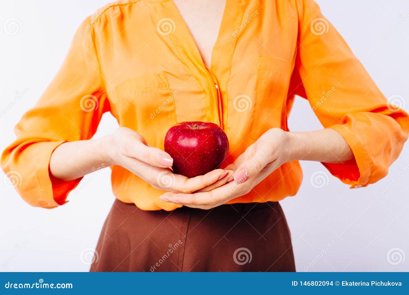 Het meisje in een heldere oranje sweater met een appel in haar handen bevordert gezond voedsel