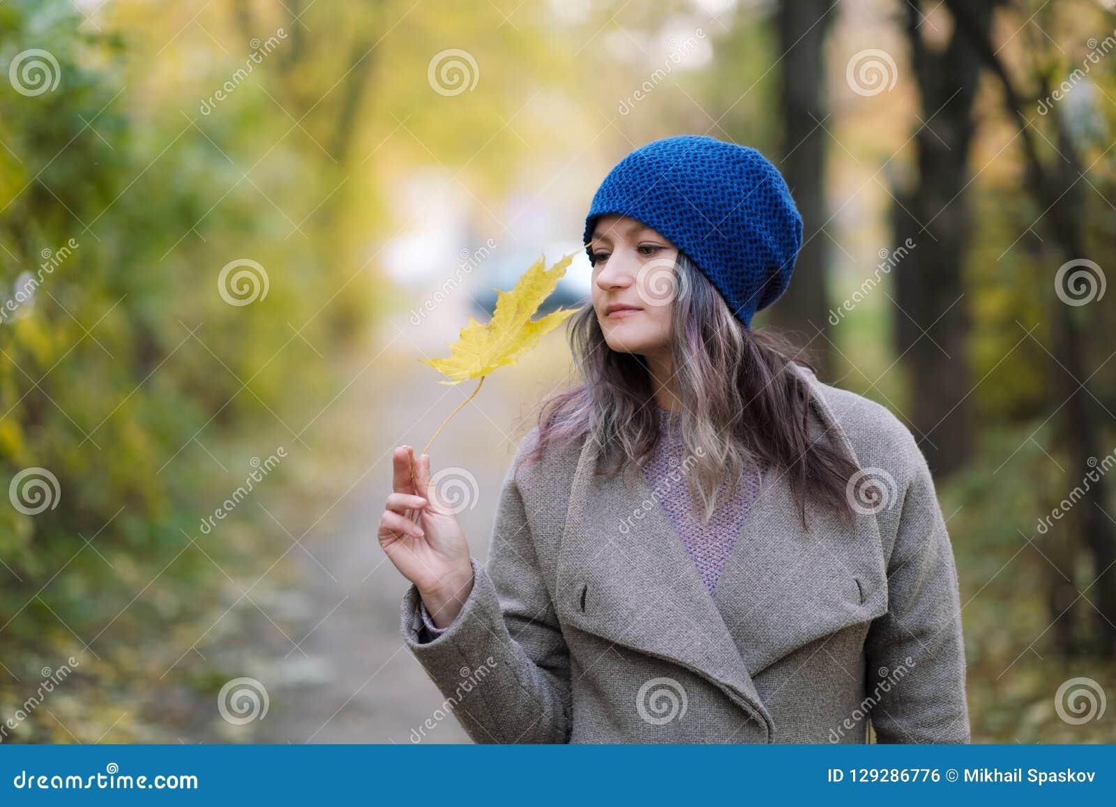 Het meisje in een laag en een blauwe hoed op een achtergrond van de herfstbomen en esdoorn gaat weg