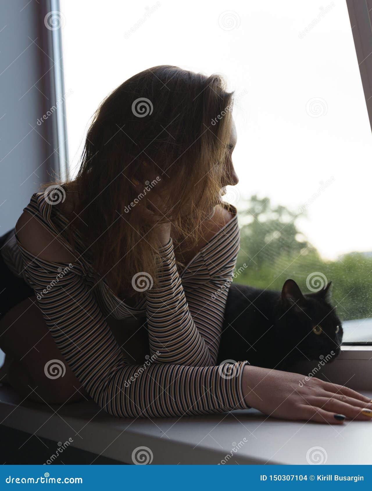 Het meisje in een rok en een kat zitten op het venster op de straatavond