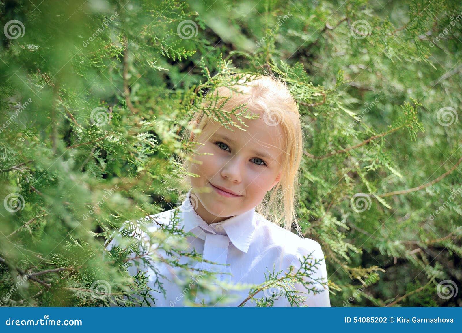 Het meisje in een tuin kijkt uit wegens gebladerte