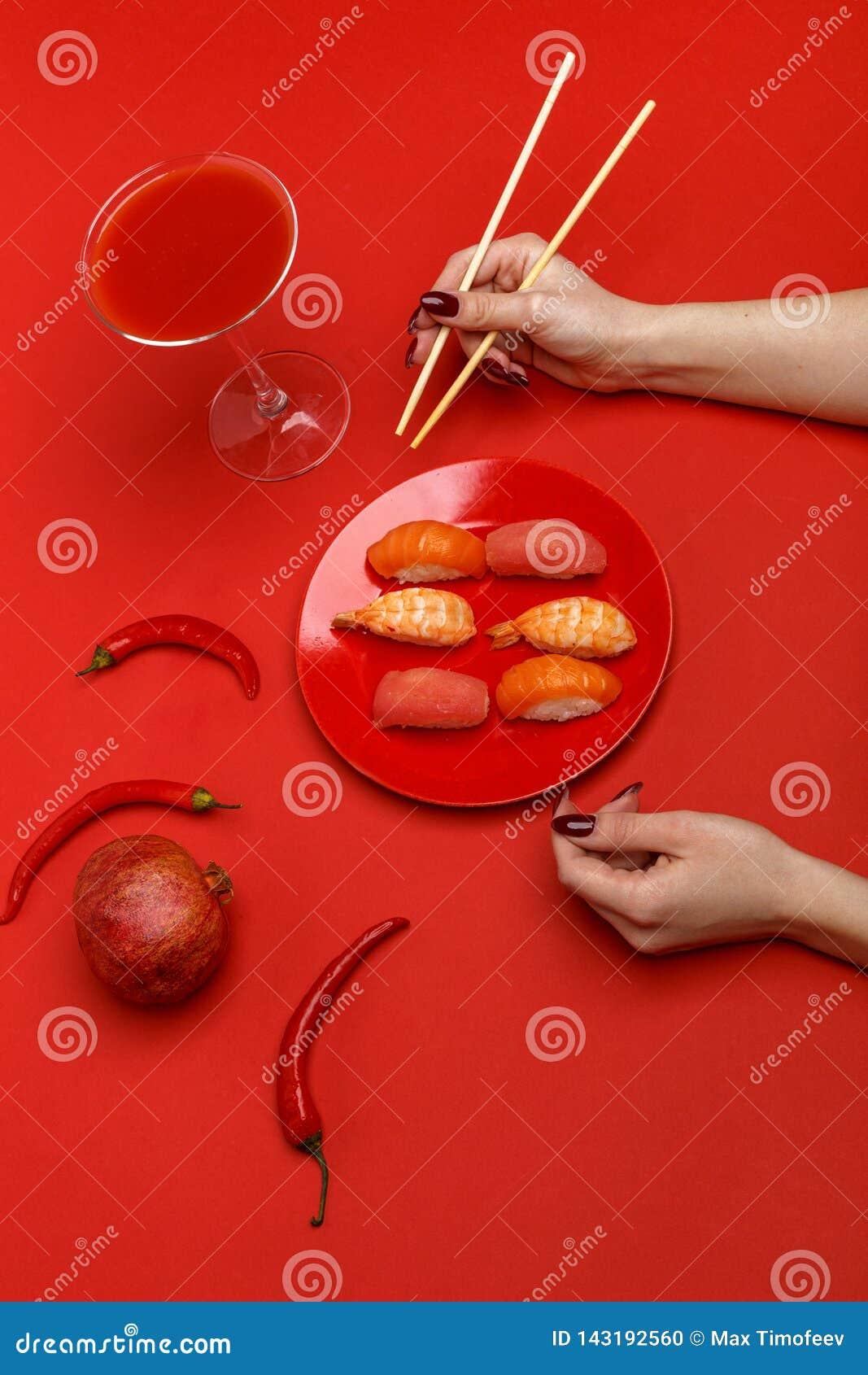 Het meisje eet sushi op een rode plaat Creatief concept restaurantlijst het plaatsen