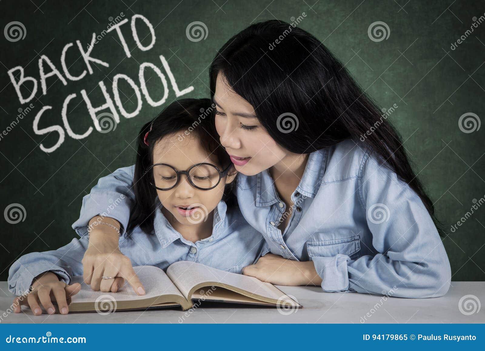 Het meisje en de leraar lezen een boek