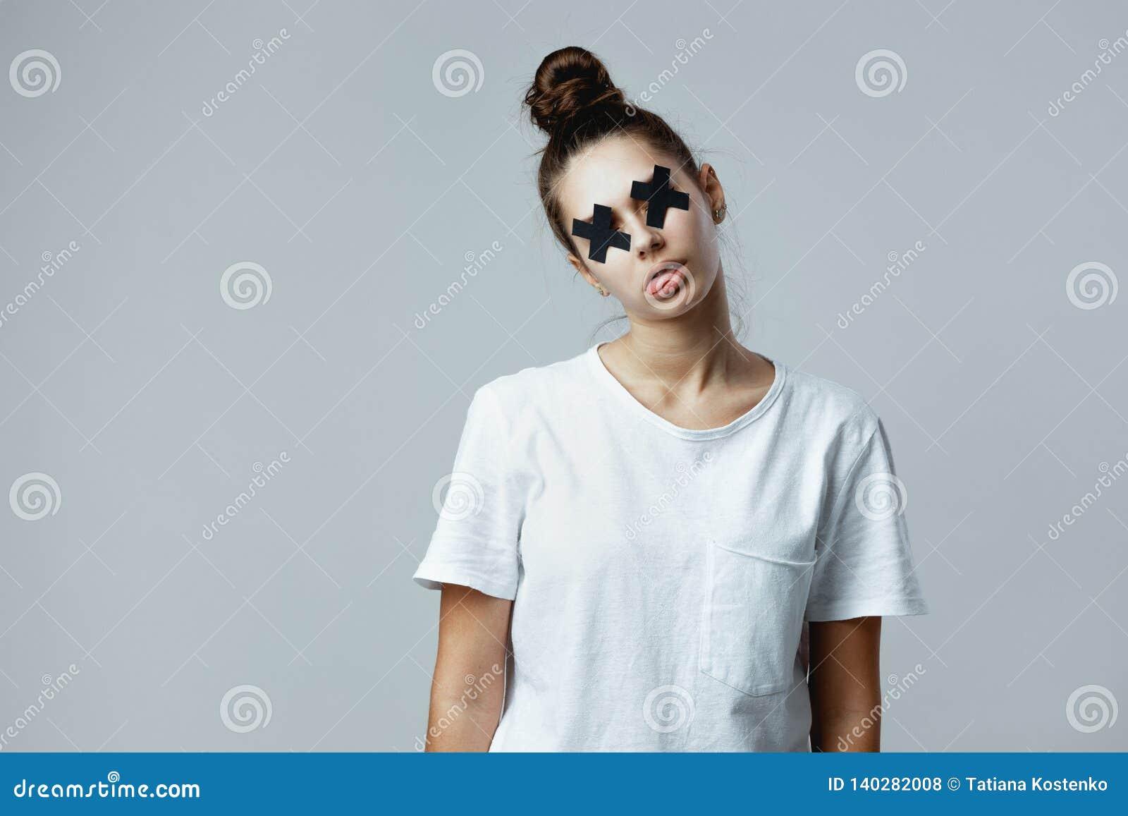 Het meisje gekleed in witte t-shirt met zwarte kruisen van plakband op de ogen stelt als een zombie op het wit