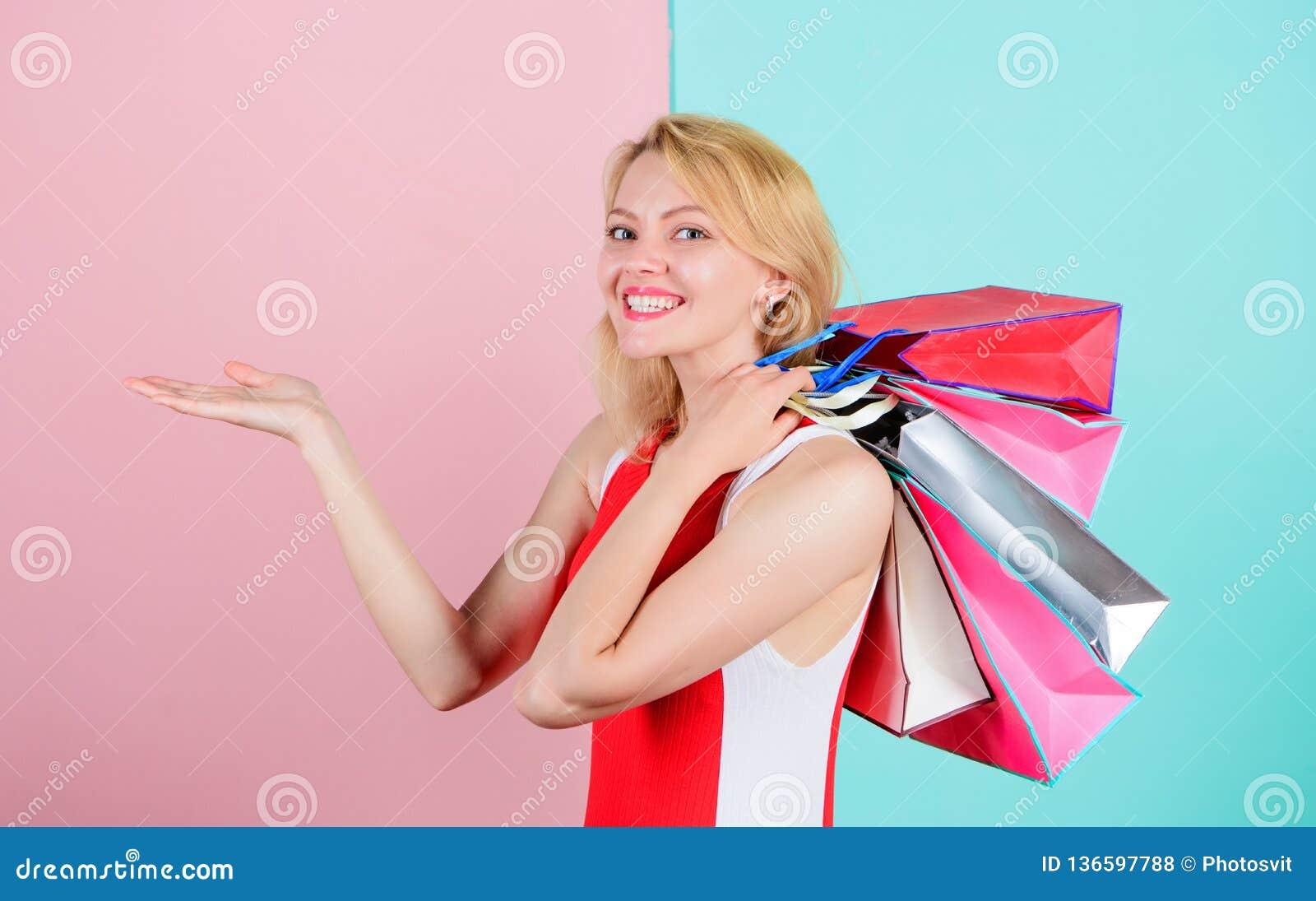 Het meisje geniet van het winkelen of enkel gekregen verjaardagsgiften De greepbos van de vrouwen rode kleding het winkelen zakke