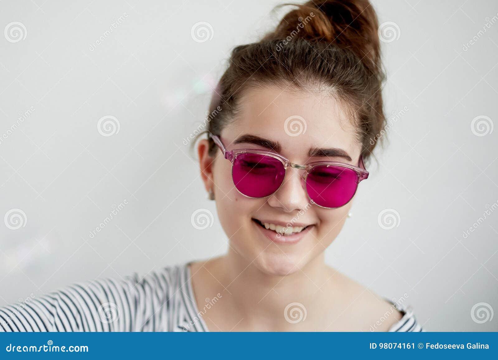 Het meisje glimlacht gelukkig in de roze glazen Een naïeve mening van de wereld in de overgang naar volwassenheid