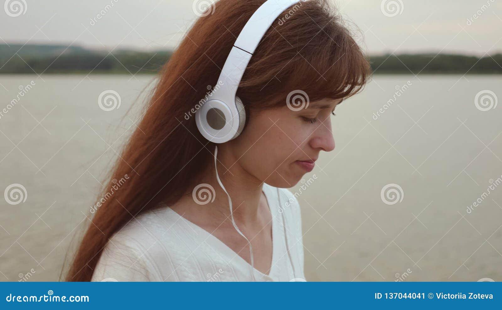 Het meisje in hoofdtelefoonsgangen langs strand met tablet en luistert aan muziek, de post van meisjescontroles op een online tab