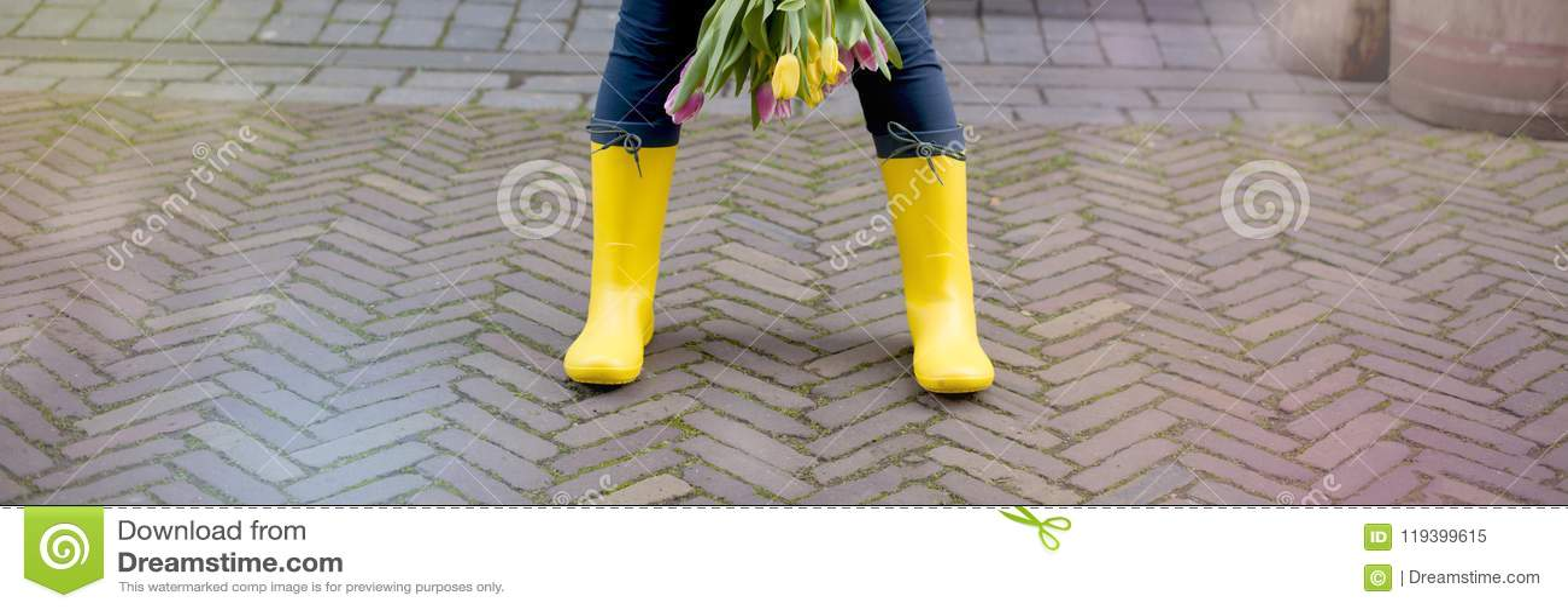 Het meisje houdt een boeket van verse de lentetulpen Straat van de oude stad Gele rubberlaarzen Vrije ruimte voor tekst