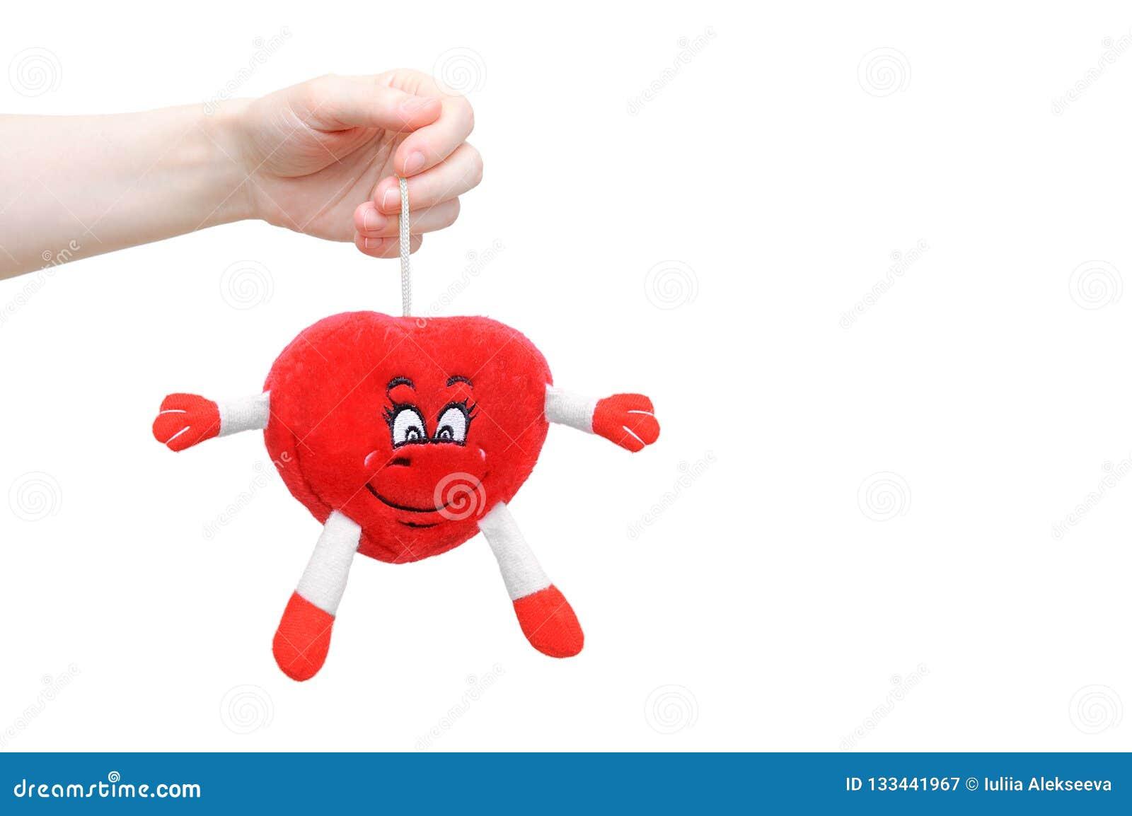 Het meisje houdt in haar hand een zacht stuk speelgoed in de vorm van een hart