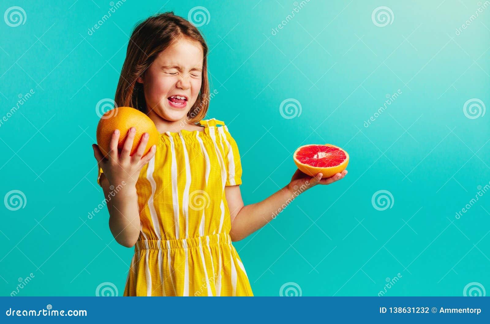 Het meisje houdt niet van de smaak van grapefruit