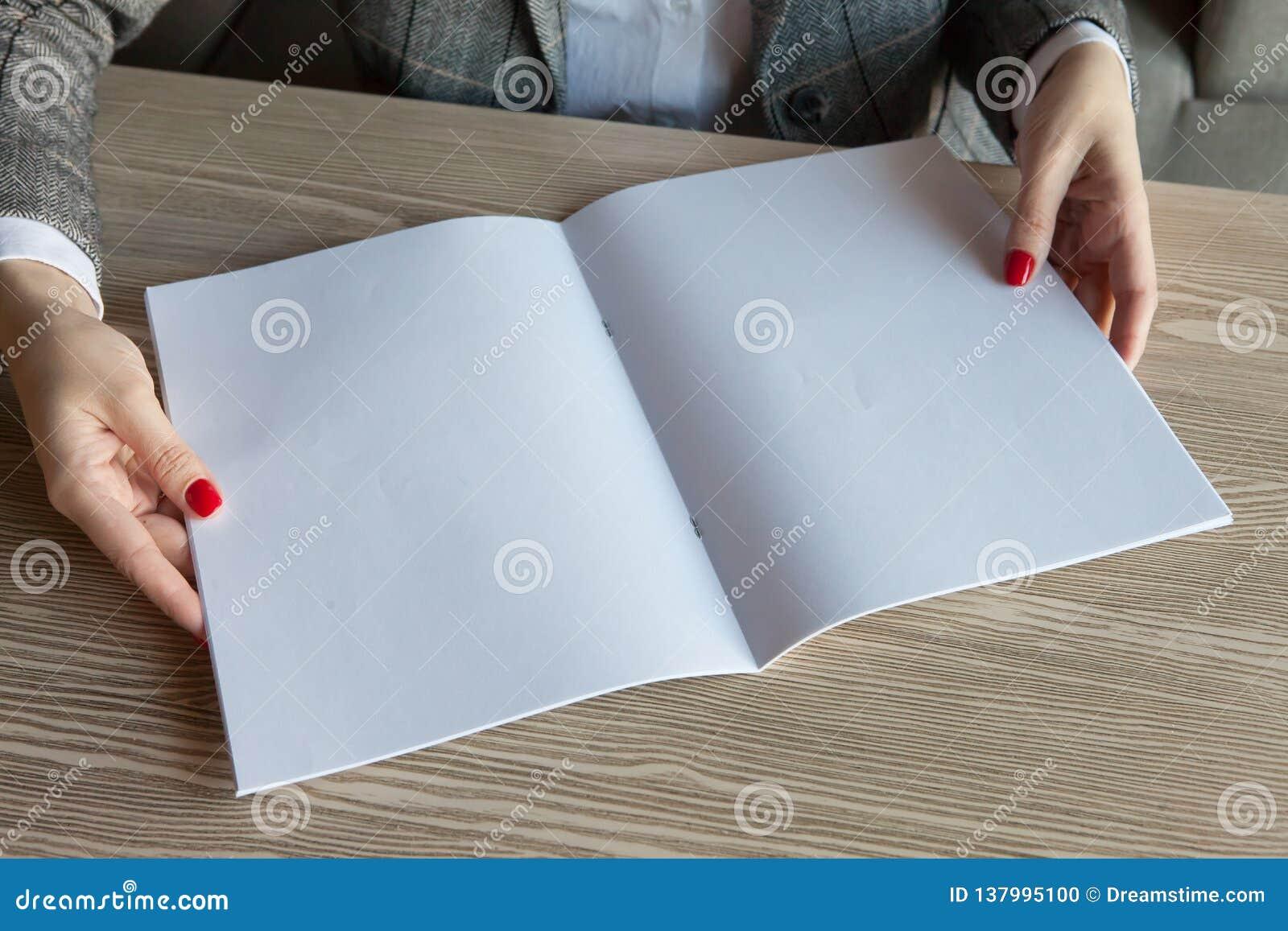 Het meisje houdt ter beschikking het tijdschriftmodel het A4-formaat