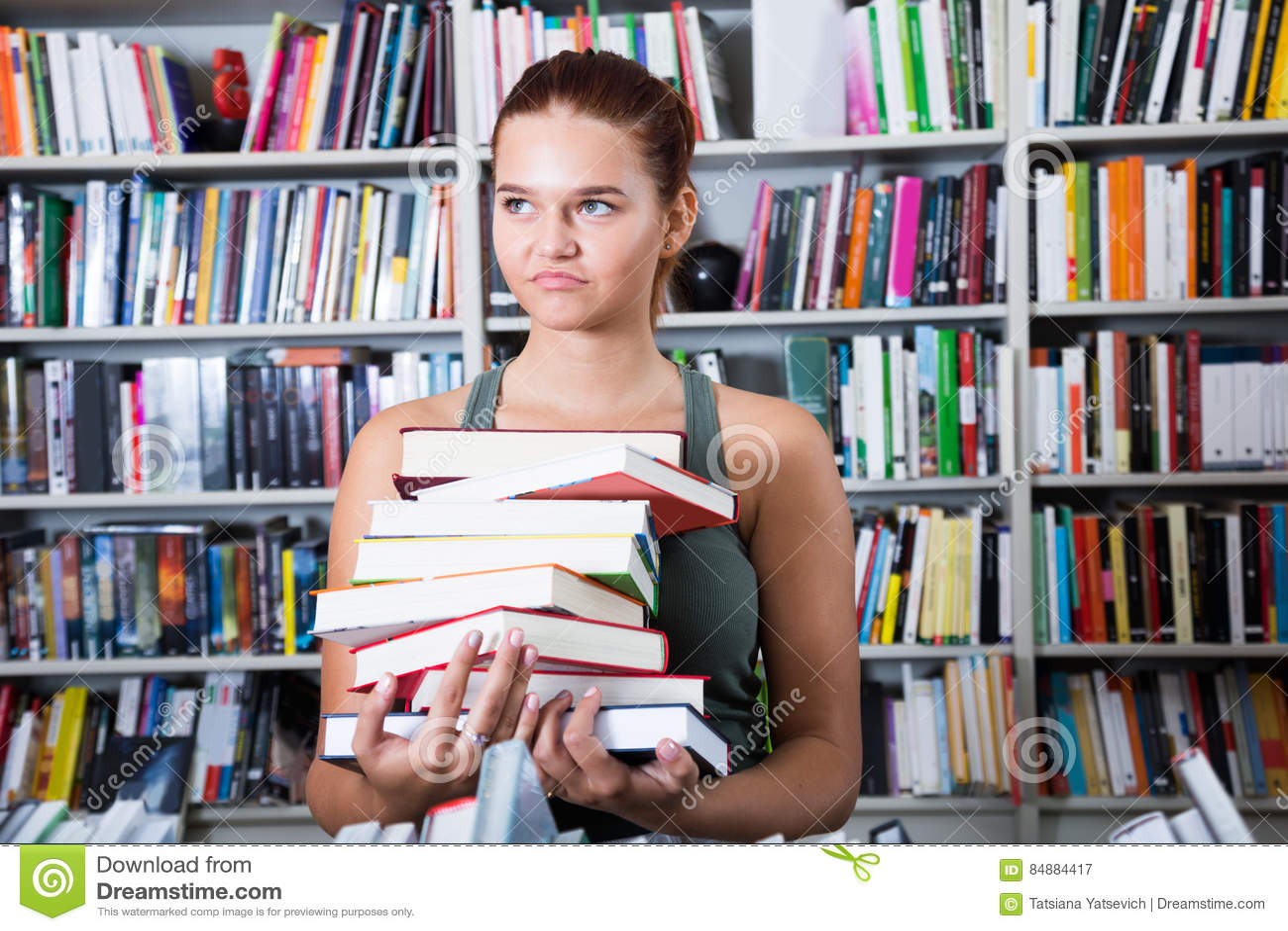 Het meisje kiest een boek in universitaire bibliotheek