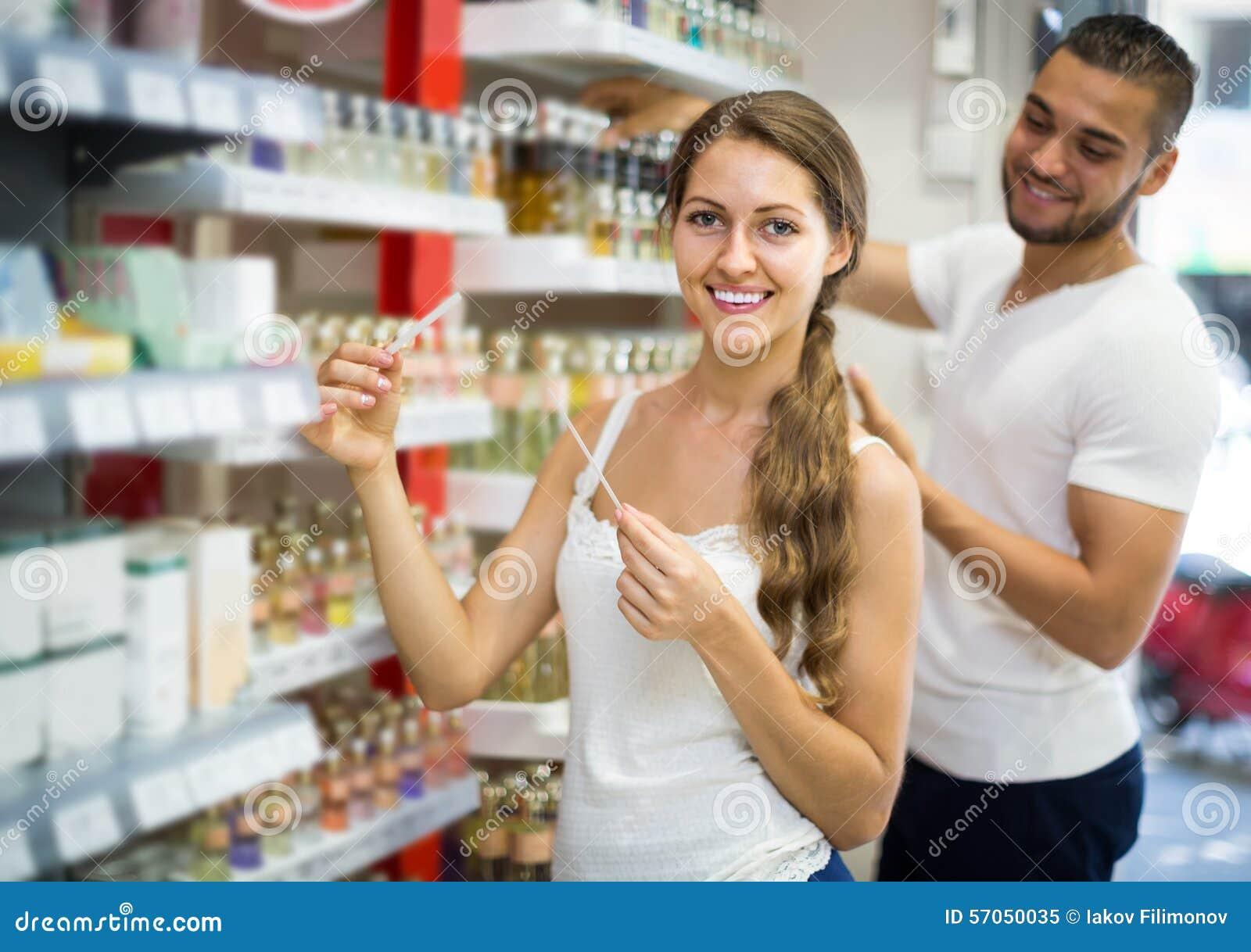 Het meisje kiest parfum in de winkel