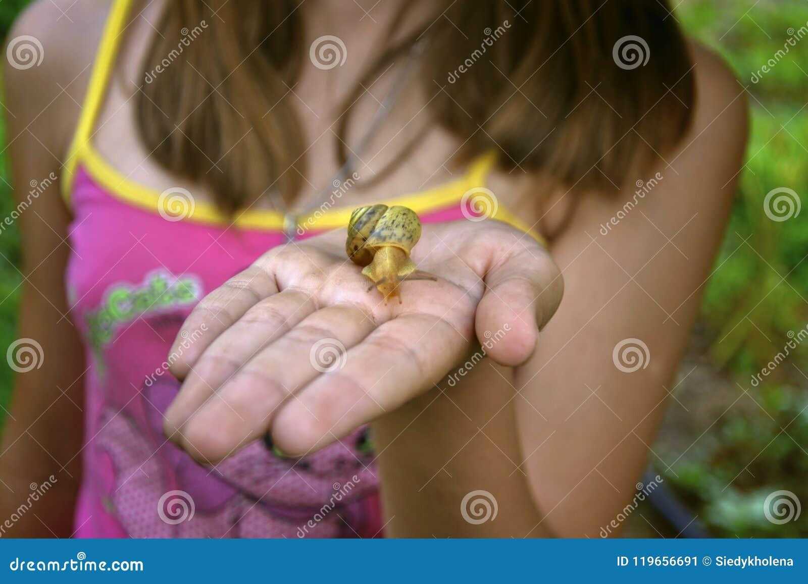 Het meisje kijkt en houdt een slak