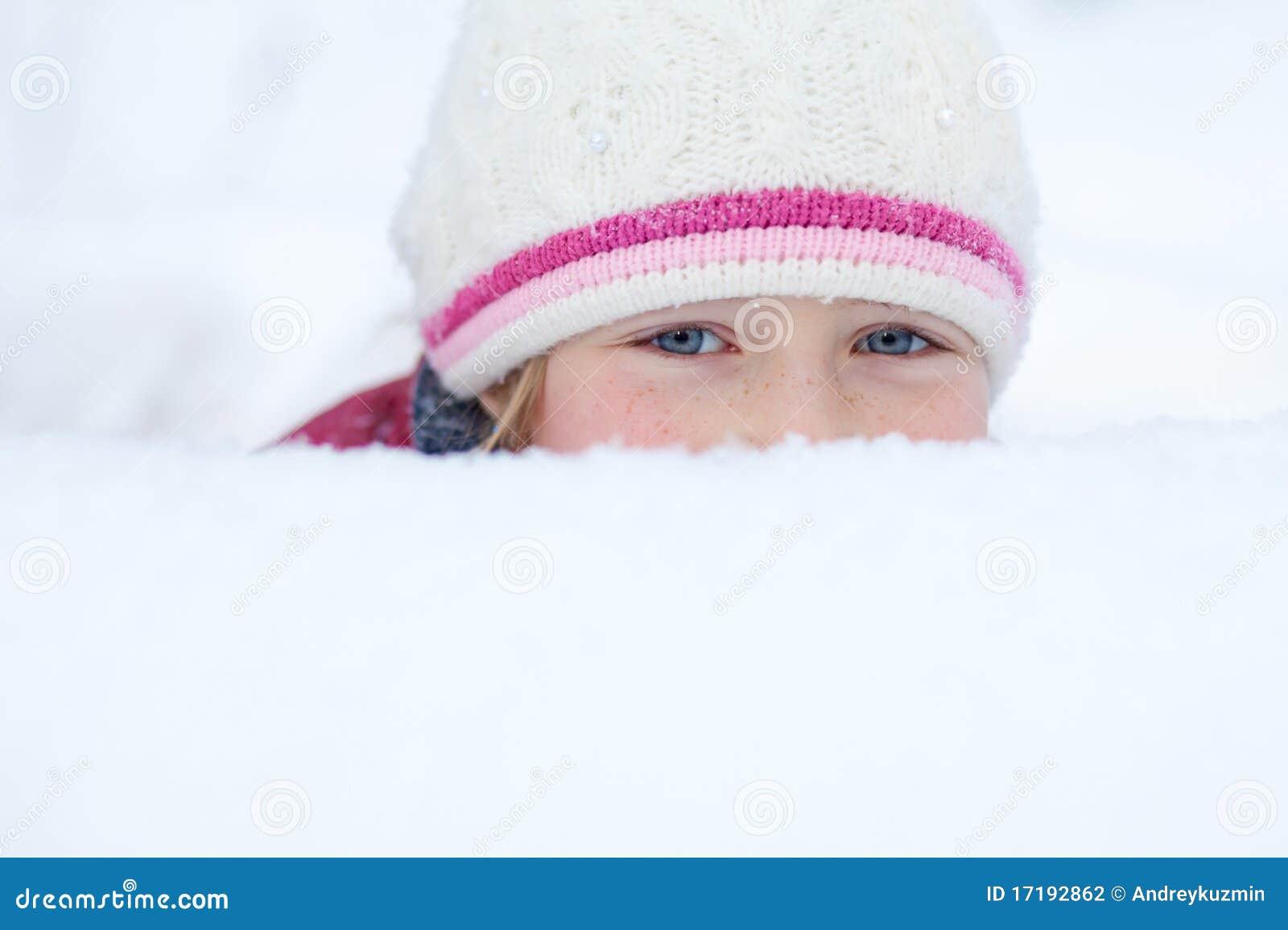 Het meisje kijkt uit sneeuwbank met smileyogen
