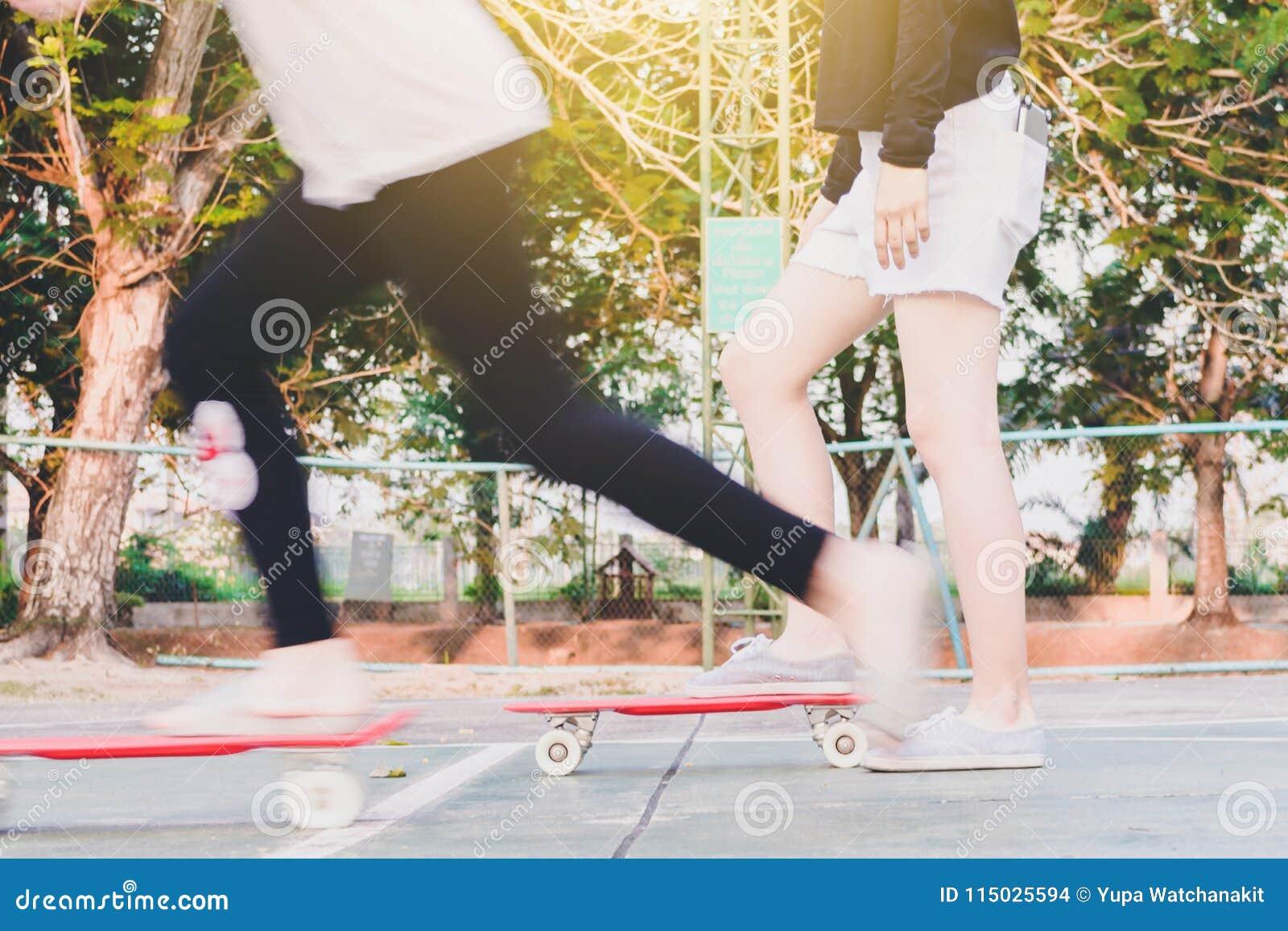 Het meisje is klaar aan het ertoe brengen van begin om na zustermovin met een skateboard te rijden