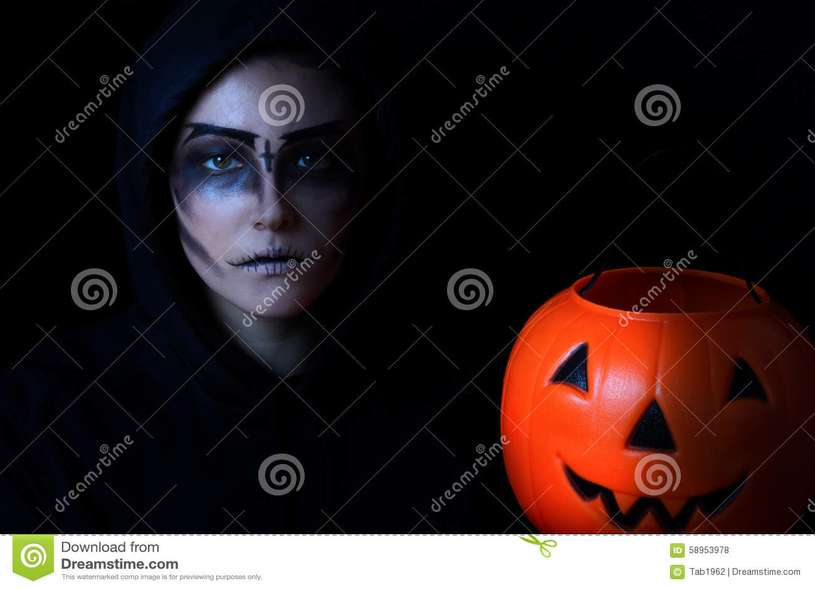 Het meisje kleedde zich in enge gezichtsverf met pompoenemmer op zwarte bedelaars