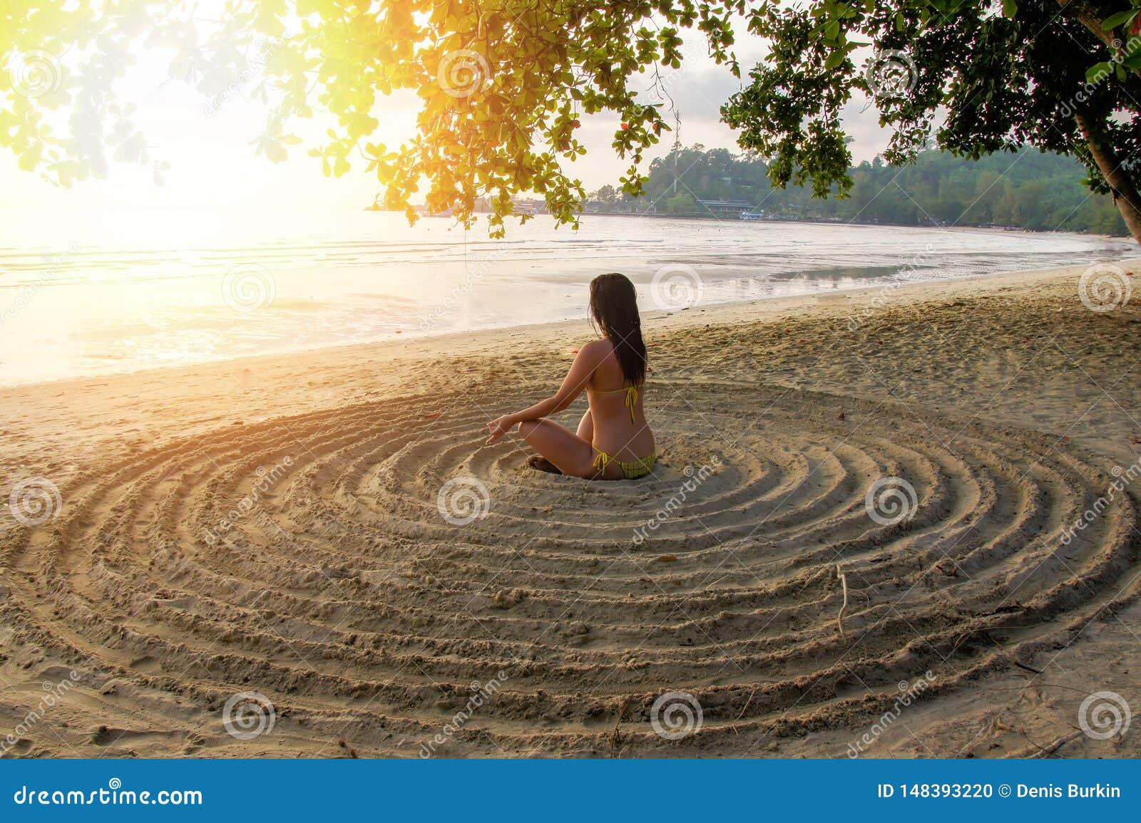 Het meisje leunt op het zandige strand in het centrum van een onvoorbereide cirkel achterover en mediteert