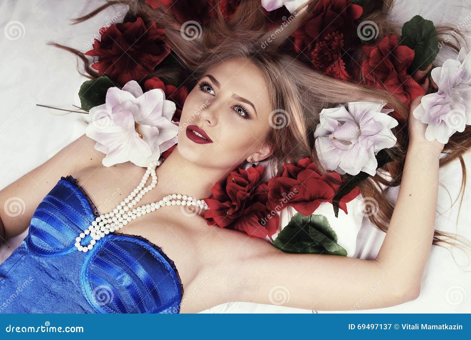 Het meisje ligt in bed door bloemen wordt omringd die