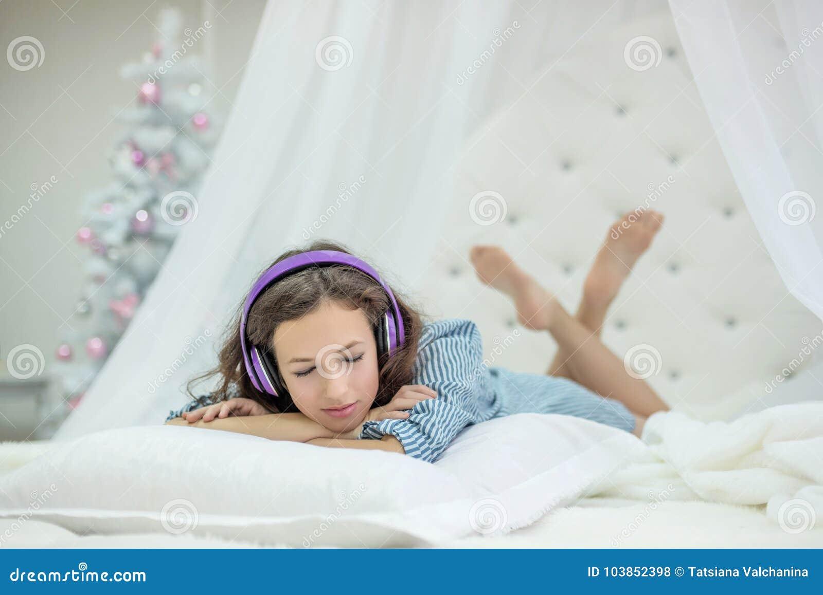 Slaapkamer Meisje Jaar : Het meisje ligt op een hoofdkussen op een wit rond bed en luistert