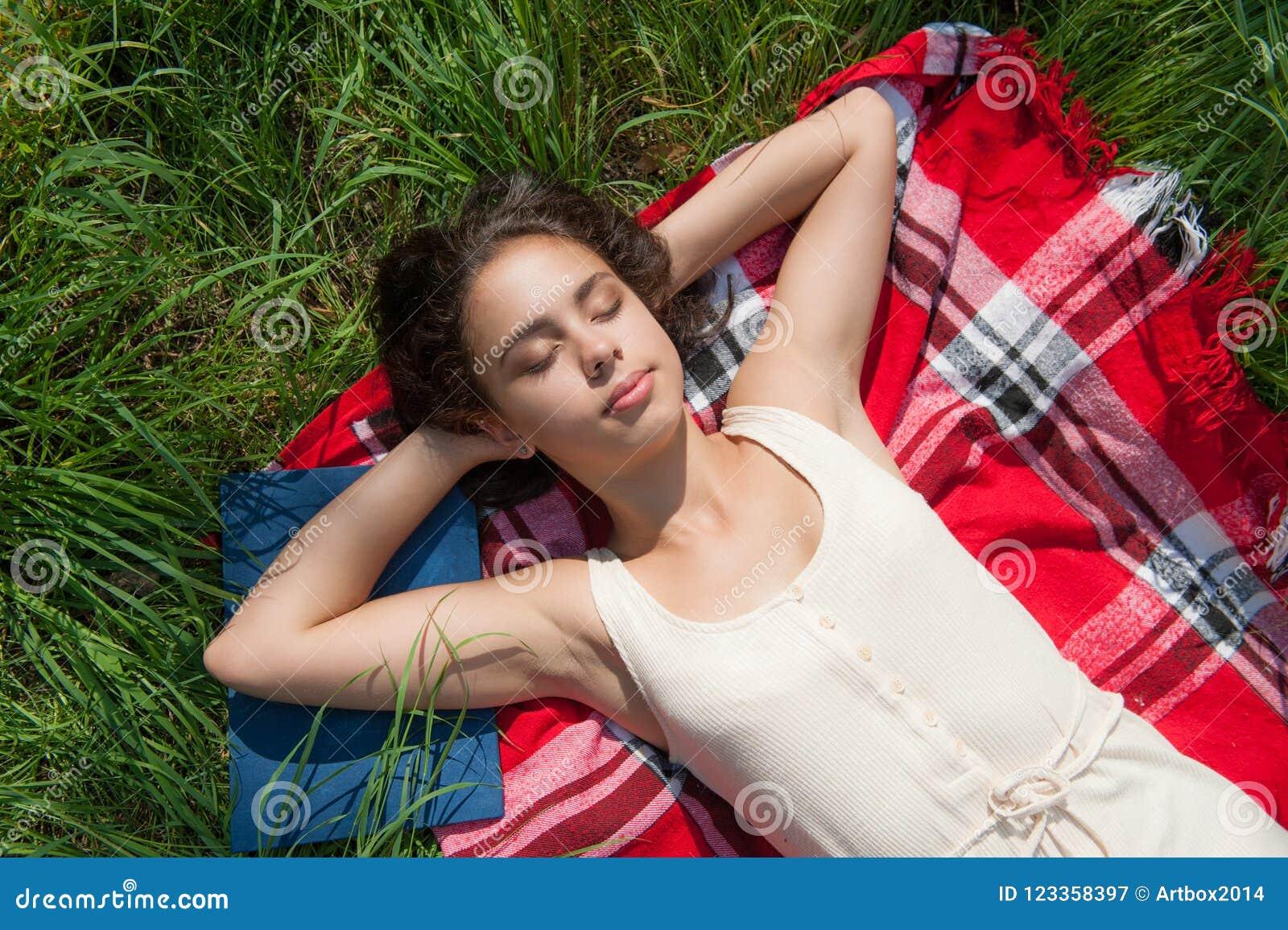 Het meisje ligt op een plaid op het gras