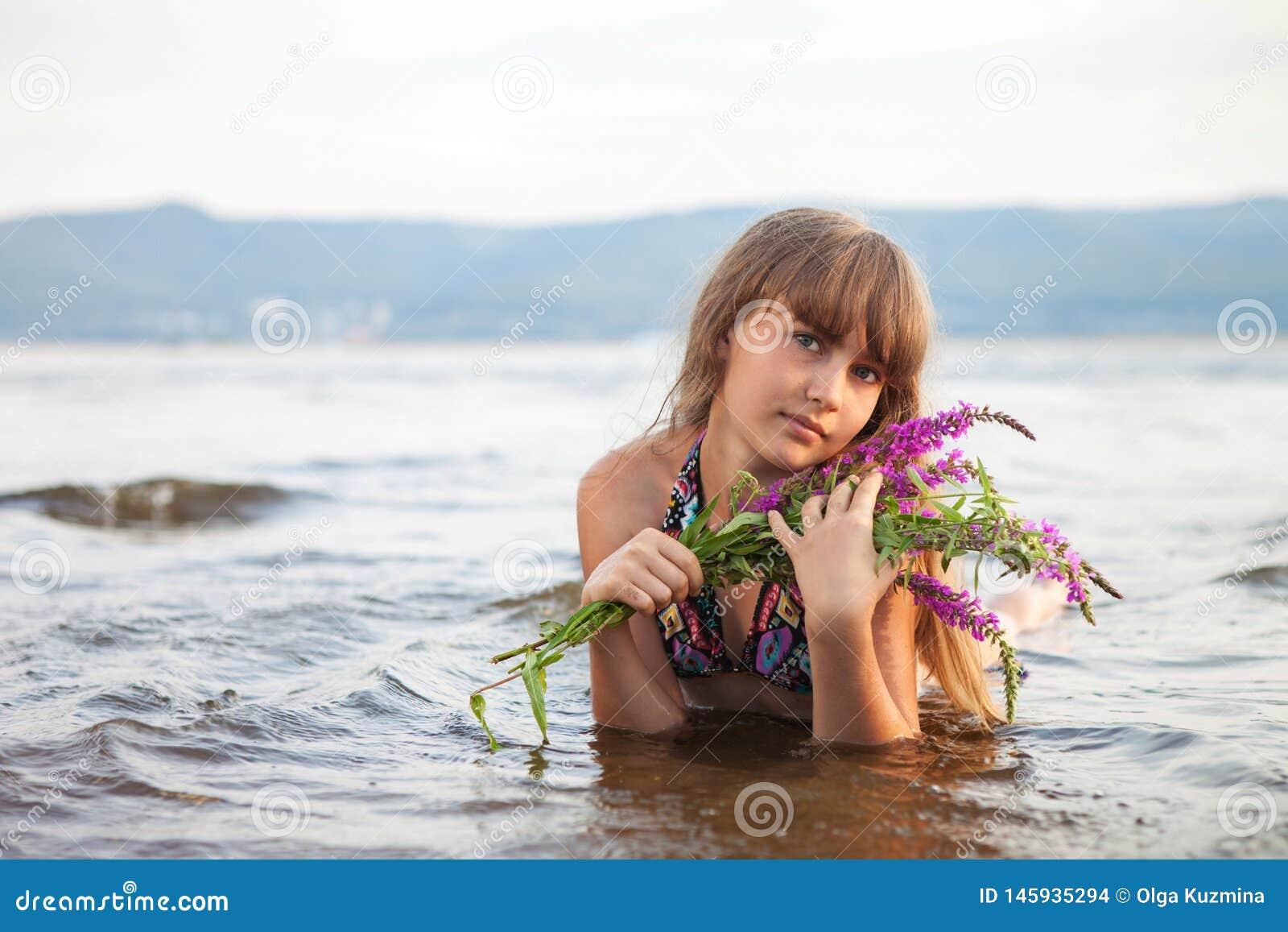 Het meisje ligt op het strand met een boeket van kleur Mooie mening, de zomerdag