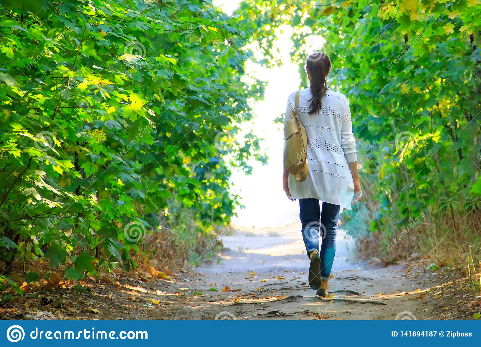 Het meisje loopt langs de weg in het hout aan het licht