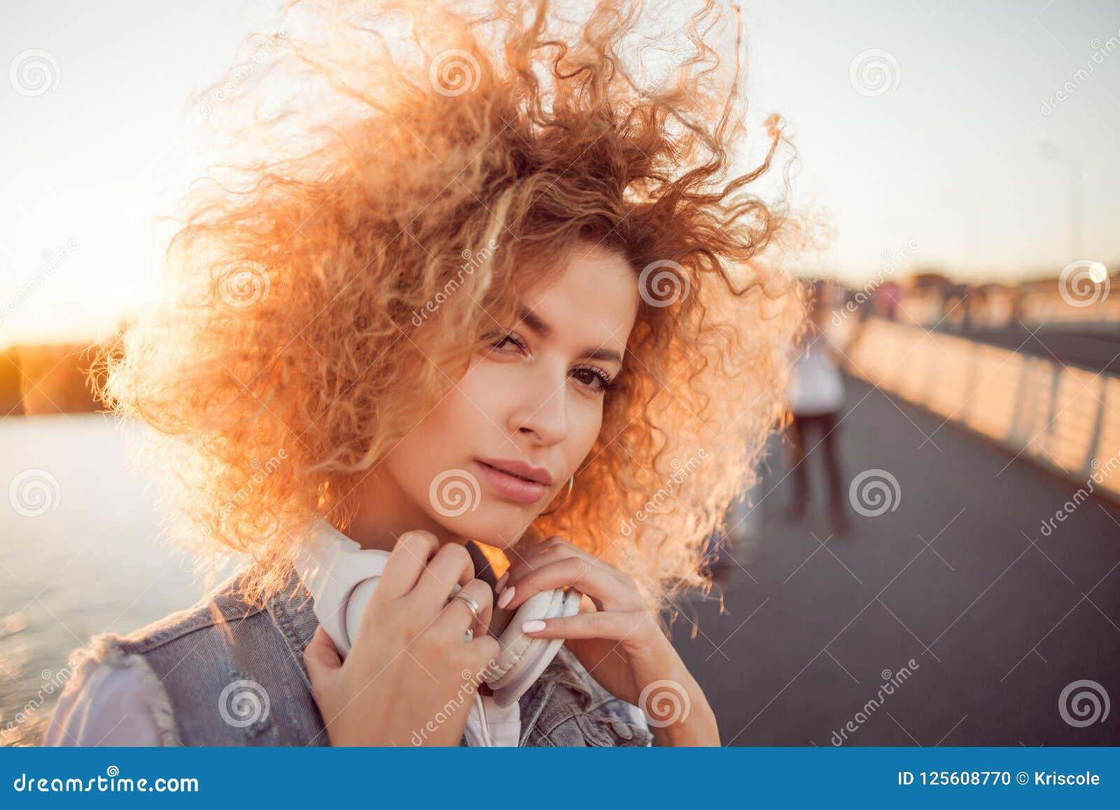 Het in meisje met grote hoofdtelefoons op een stadsgang, sluit omhoog