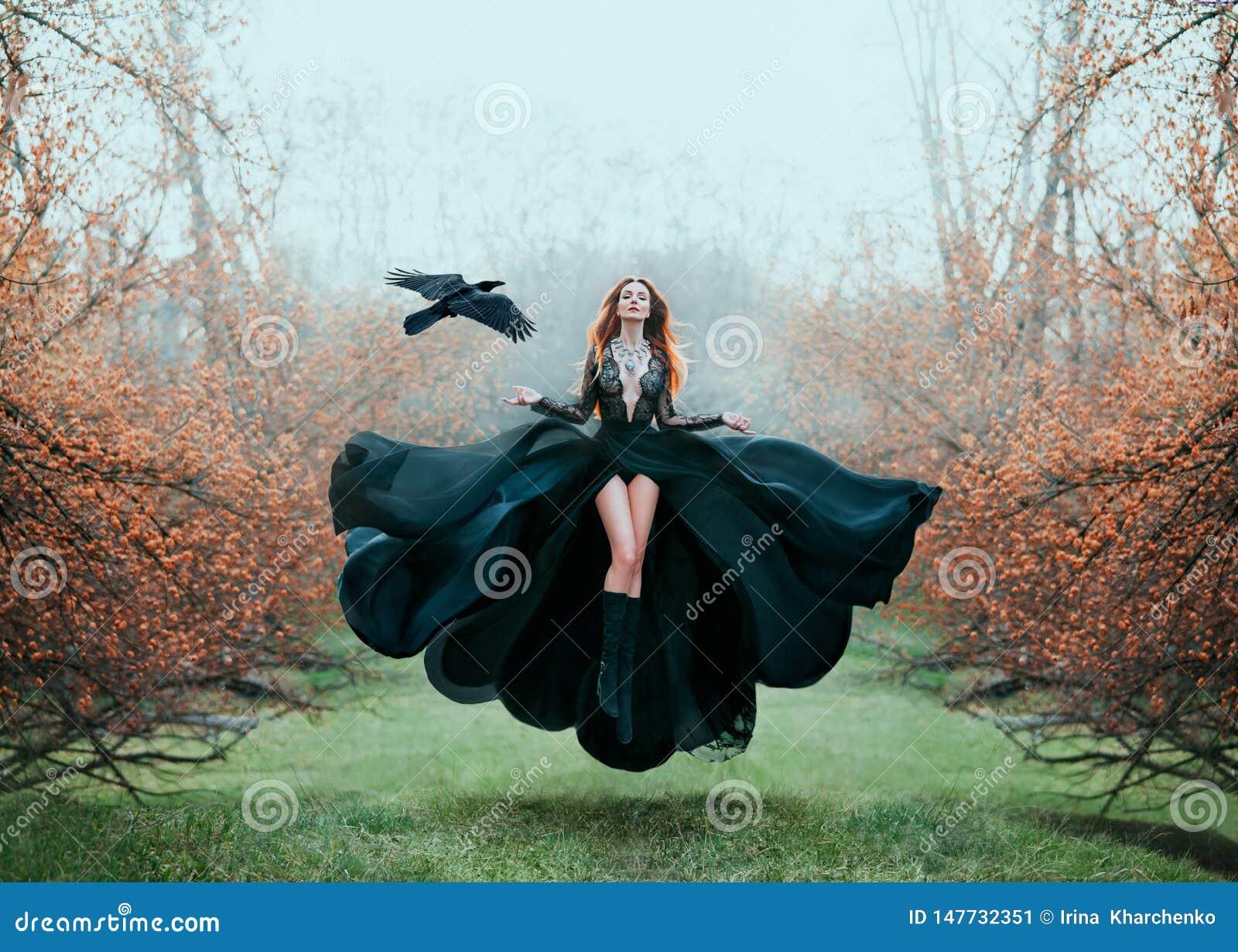 Het meisje met helder rood haar levitatie ondergaat boven grond, krachtige tovenares, bosgodin in zwarte vliegende kleding met ka