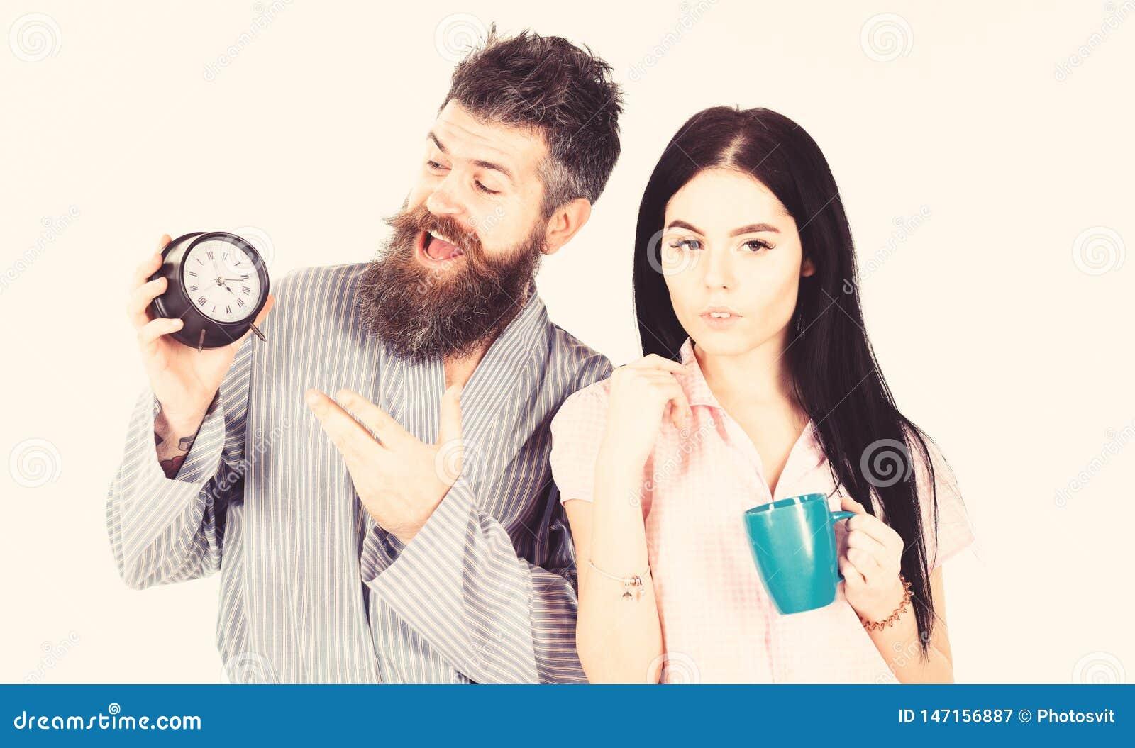 Het meisje met koffiekop, mens houdt klok in hand Het paar, familie ontwaakte op tijd Paar in liefde, jonge familie in pyjama