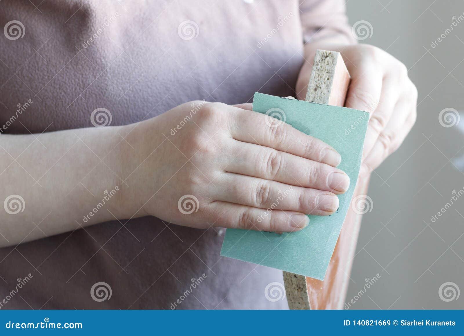 Het meisje met schuurpapier poetst spaanplaat, triplex op Close-up