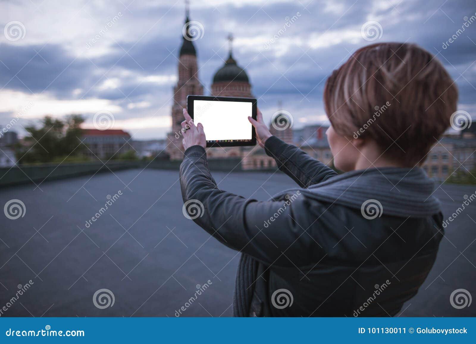 Het meisje neemt beelden van de stad op een tablet
