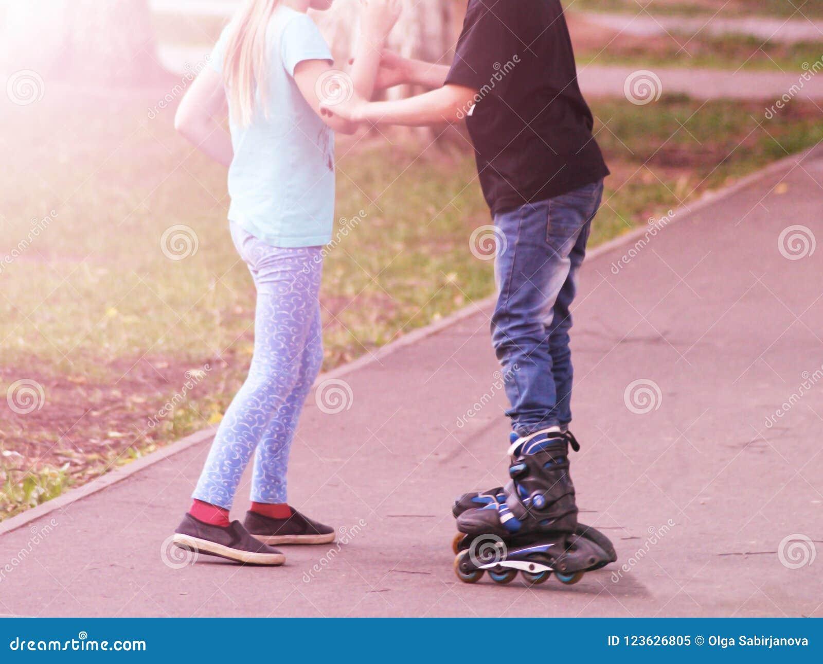 Het meisje onderwijst de jongen om op rolschaatsen bij zonsondergang te berijden