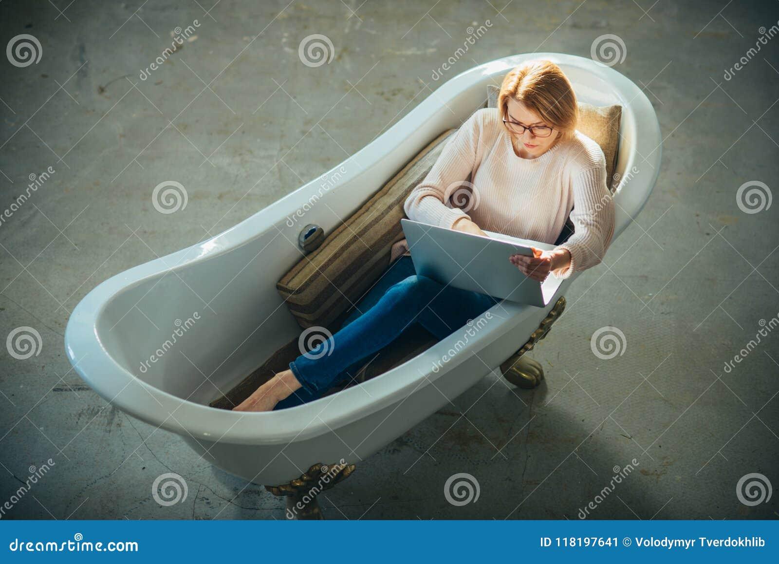 Het meisje ontspant in badkuip met laptop houdt blog Behendige zaken en mededeling Koop online en digitale marketing