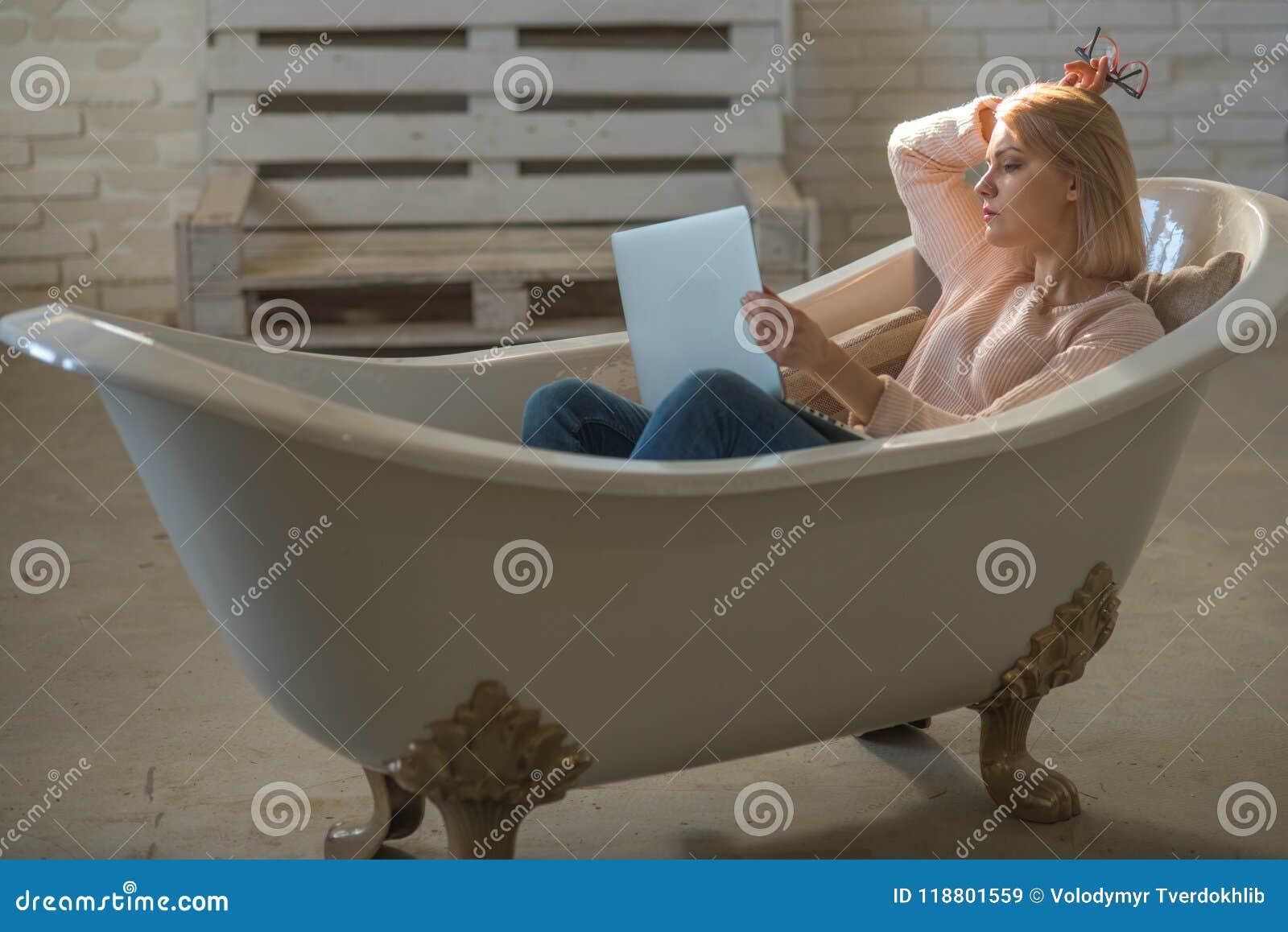 Het meisje ontspant in badkuip met laptop houdt blog Het vrouwenwerk aangaande computer in huisbad Behendige zaken en mededeling