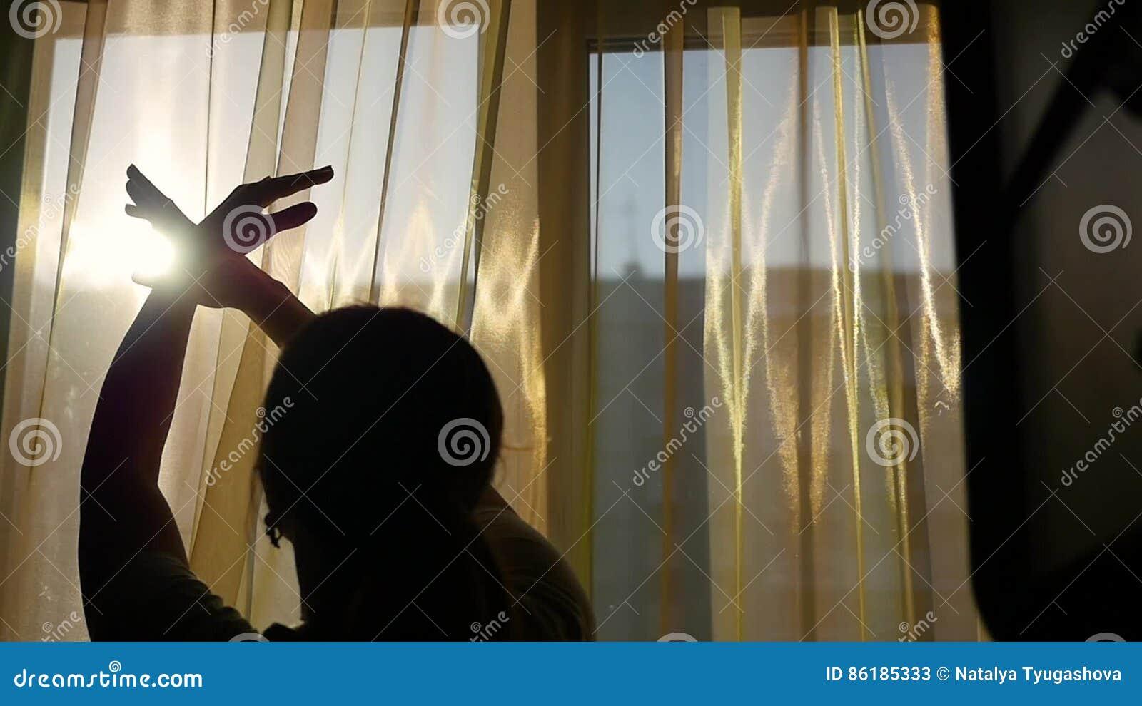 https://thumbs.dreamstime.com/z/het-meisje-opent-de-gordijnen-en-met-zijn-handen-door-de-zon-s-stralen-die-speelt-silhouet-van-een-meisje-86185333.jpg