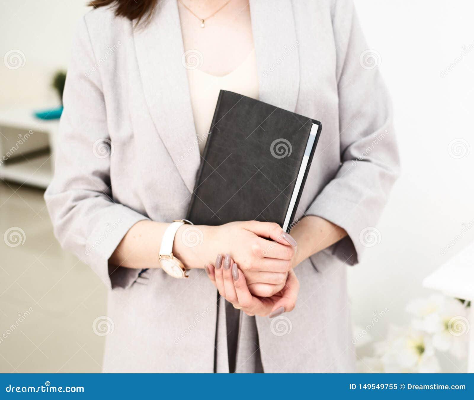 Het meisje overhandigt een boek in haar handen, gekleed in grijs jasje Zij heeft een polshorloge op haar hand Witte achtergrond