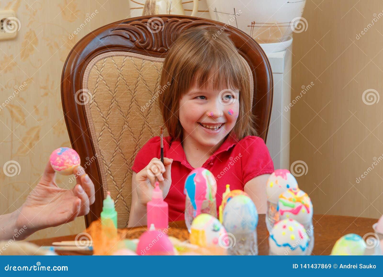Het meisje is pret het schilderen eieren voor Pasen