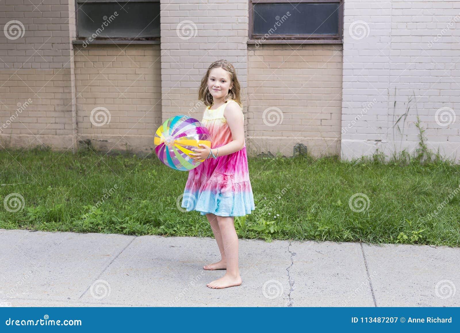 Het meisje in regenboog kleurde kleding en naakte voeten houdend duidelijke vinylstrandbal