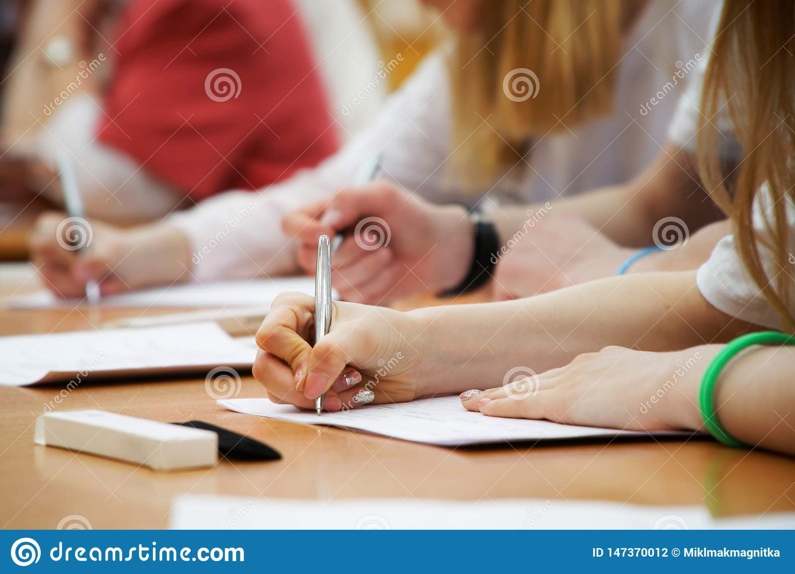Het meisje schrijft met een vulpen op een stuk van document tijdens klassen bij school of universiteit Onderzoek, examens