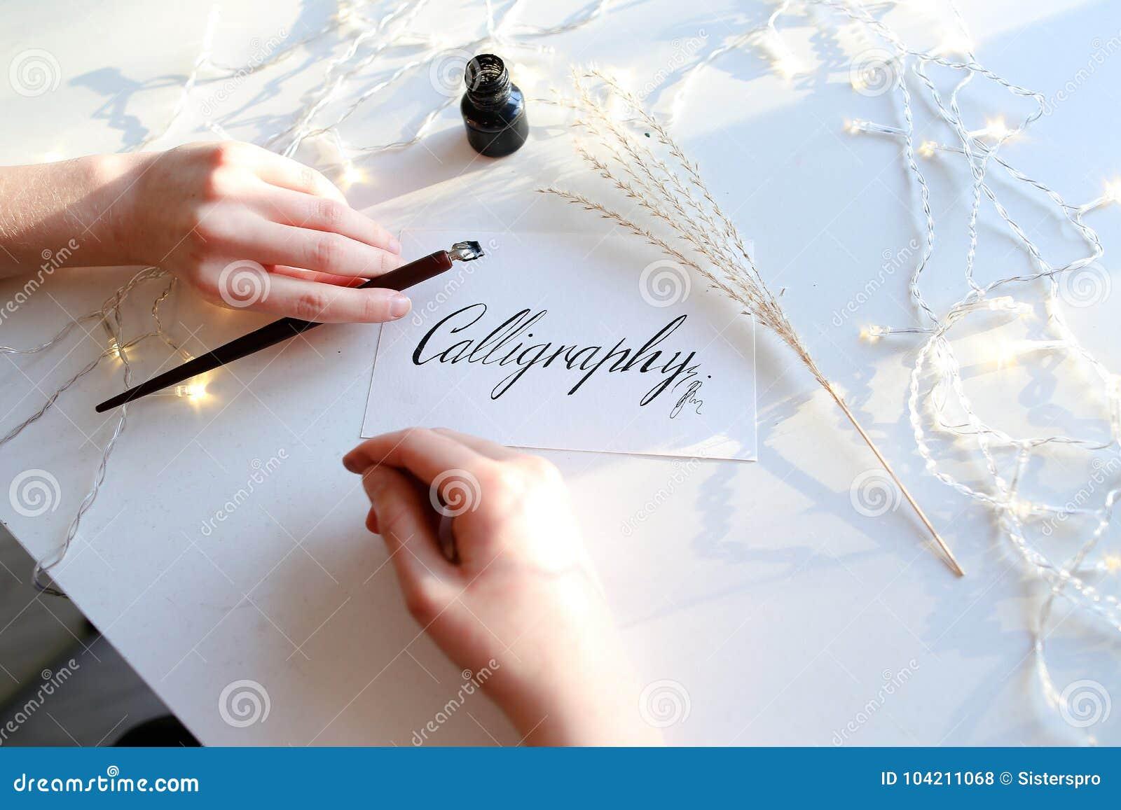 Het meisje schrijft penfontein kalligrafische brieven, zittend bij lijst
