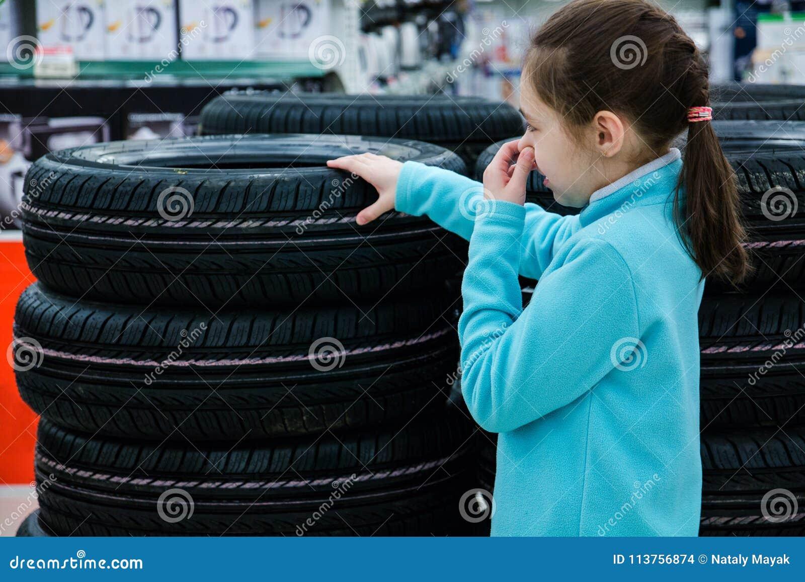 Het meisje sluit haar neus van de onplezierige geur van rubber, vermoeit op het winkelvenster voor verkoop