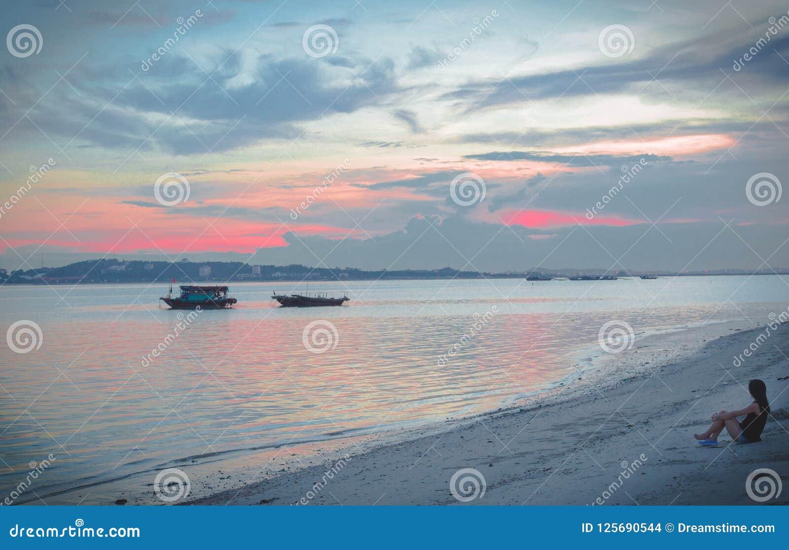 Het meisje is smoorverliefd vóór zonsondergang in de Lange Baai van Ha